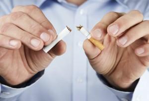 quit smoking. Smoker breaking smoke in two